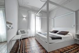 Светлая и комфортная спальня, контрастирующая с черными, белыми и древесными оттенками в апартаменах Casp в Барселоне