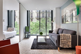 An avant-garde colorful living room with big windows and beautiful flooring in habitat Pedrera apartment in Barcelona
